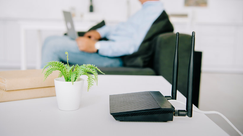 Router device on a desk with a person holding a laptop.